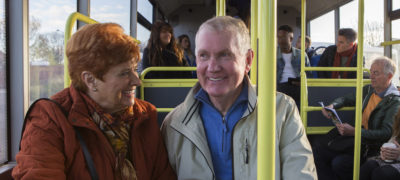 Senior couple travelling on the bus. There are other people sat on the bus who are in the background.