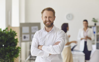 Portrait of happy successful handsome businessman in office workspace. Confident bearded businessman or head of company department standing arms crossed looking at camera and smiling