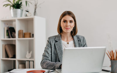 Business woman in checkered jacket looking at camera with smile while sitting at desk in her office
